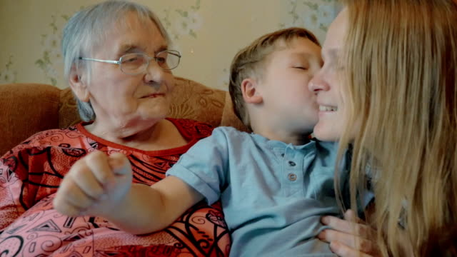 Little boy expressing love to mother and grandmother with kisses video