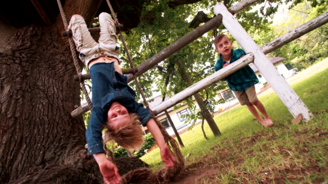 Little boy hanging from a rope ladder smiling at camera video