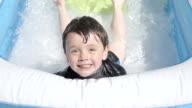 Little Boy Having Fun In A Paddling Pool Slow Motion video