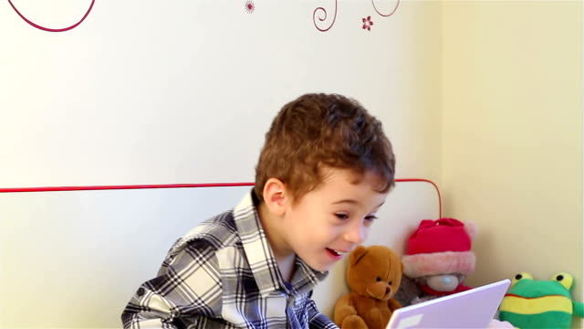 Little boy having fun on laptop video