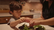 A little boy helping his mom prepare food in the kitchen video