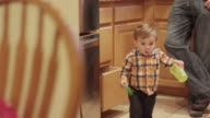 Little boy holding a plastic dish in the kitchen runs toward their dog video