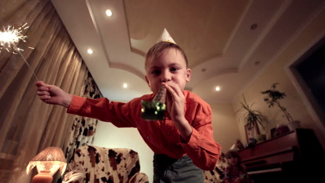 Little boy holding sparkler and blowing whistle video