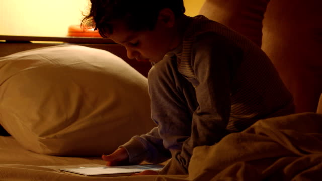 Little boy in a night-suit uses a tablet PC in a bed video
