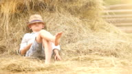 Little boy in a straw hat naps in the stack of hay taking a break from his choirs video