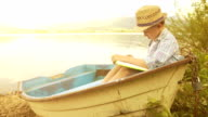 Little boy in a straw hat sitting in the rustic boat reading a book video