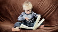 Little boy in glasses reading book video