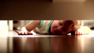 Little boy is looking for something under the bed video