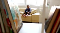 Little boy jumps into cosy sofa with his favorite book video