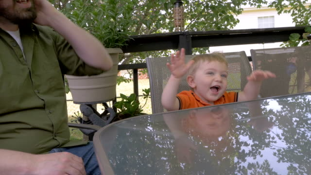 A little boy laughing, smiling, and clapping with his father sitting at a table video