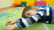 Little boy laying on the floor and playing with car video