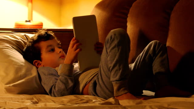 Little boy lays and touches on a tablet PC at home video