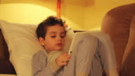 Little boy lays in a bed and looks at a tablet PC at home video