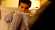 A little boy lays in a bed and looks at a tablet PC video