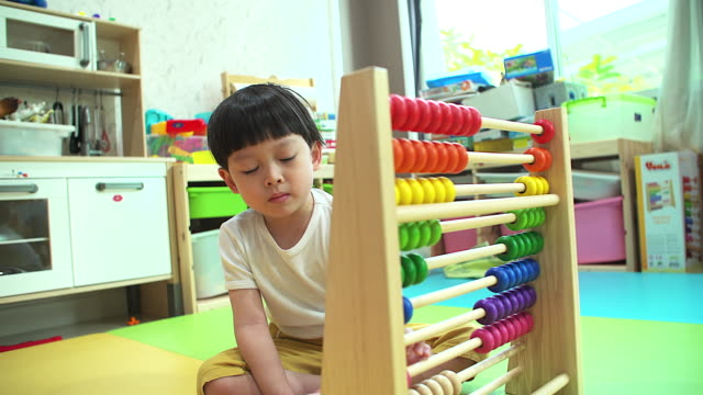 4K: Little boy learning by counting with abacus at his home. video