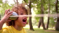 Little boy listening to sound through a tin can phone video
