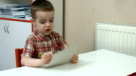 Little boy looking at and studying video