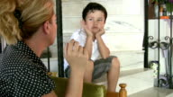 Little boy looking at his mother while smoking cigarette video