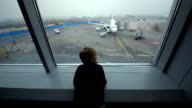 Little boy looking out the window at airport video