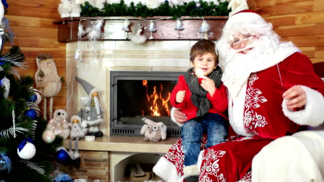 little boy on Santa's lap, child and saint nicolas holding sparkles, new year and x-mas celebration video