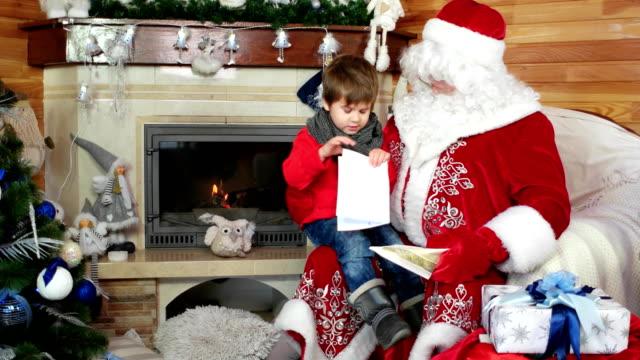 little boy open his christmas letter, child sitting on santas lap, kid visit saint nicolas residence video
