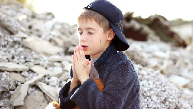 little boy orphan sitting and reading a prayer folded hands against the background of the ruins of the destroyed houses video