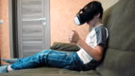 Little boy palting racing game using virtual reality headset sitting on the sofa video