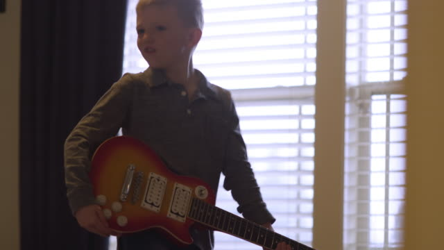 Little boy playing around with an electric guitar at home video