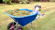 Little Boy Playing In A wheelbarrow Full Of Grass Cuttings video
