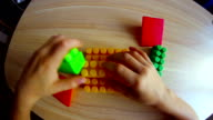 little boy playing in the colored blocks sitting at the table video