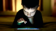 Little Boy playing on digital tablet video