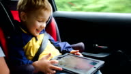 Little boy playing on tablet computer in the car video