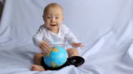 little boy playing with an  globe video
