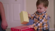 Little boy playing with cardboard blocks at home and putting them in his mouth video
