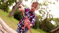 Little boy playing with dinosaur toys on log in nature video