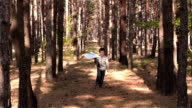 Little boy playing with paper airplane in wood. Boy running with paper airplane. Slow motion. Best childhood concept video