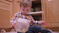 Little boy playing with plasticware in the kitchen and rubbing his eyes and looking tired video