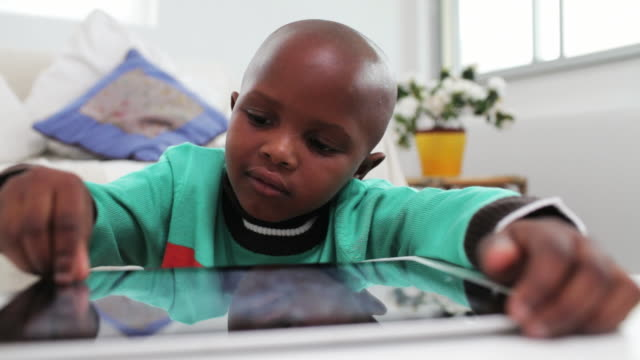 Little boy plays games on a digital tablet video