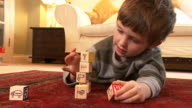 Little boy plays with stacking bricks video
