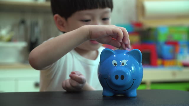 Little boy putting a coin into a piggy bank - kid saving money for future concept video