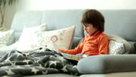 Little boy, reading a magazine, sitting on a sofa, covered with soft blanket video
