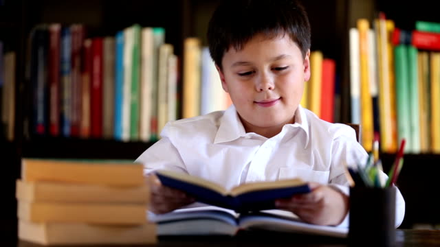 little boy reading book with a smile video
