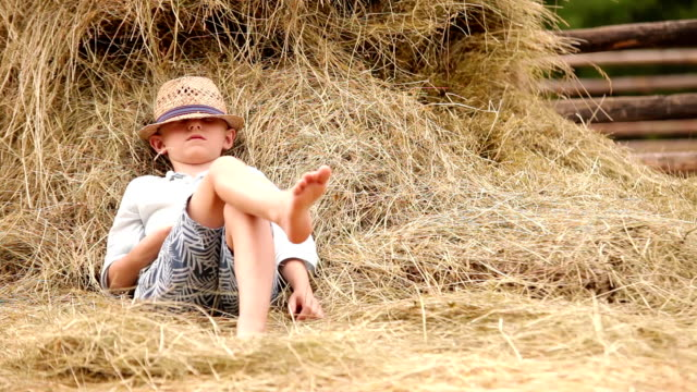 Little boy relaxing near the stack of hay video