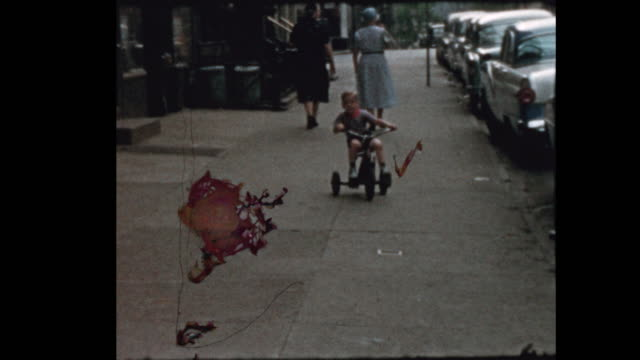 Little boy rides Tricycle down NYC street 1957 video