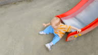 Little boy riding on a slide at the playground video