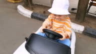 Little boy riding toy car in the park video