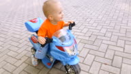 Little boy riding toy motorcycle in the park video