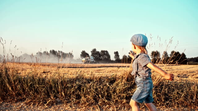 SLO MO Little boy running along cultivated field video