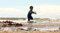 Little Boy running away From Ocean Waves video
