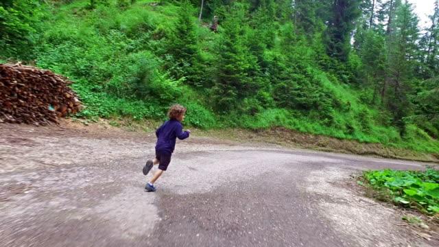 Little boy runs on mountain road - Dolomites - Italy video